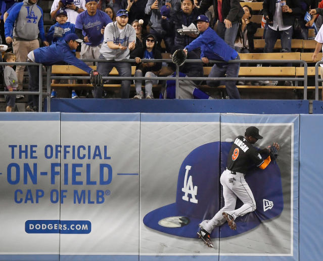 Miami Marlins center fielder Lewis Brinson runs into the wall as fans catch a ball hit for a solo home run by Los Angeles Dodgers' Enrique Hernandez during the fourth inning of a baseball game Monday, April 23, 2018, in Los Angeles. (AP Photo/Mark J. Terrill)