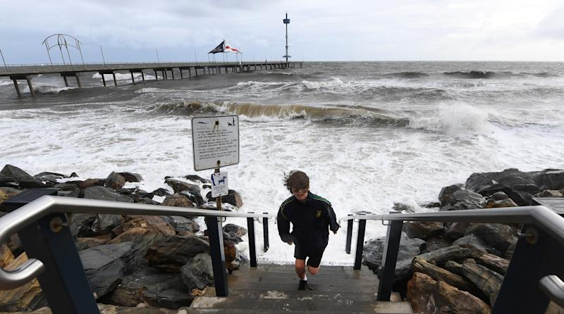 A young boy runs up steps to avoid a wave as high tide and a storm surge at Brighton Jetty, Adelaide in June 2018.