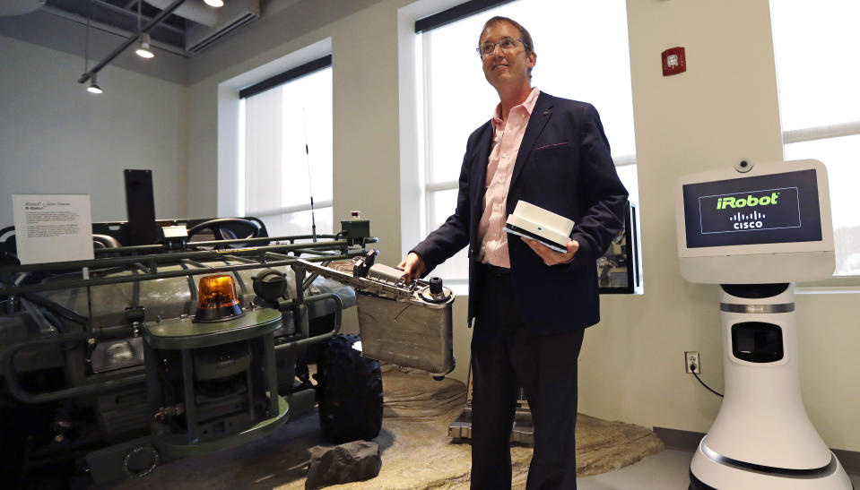 In this Thursday, Aug. 25, 2016, photo, iRobot co-founder and CEO Colin Angle holds up a Braava Jet floor cleaner and the remains of a military PackBot, which was destroyed in service with the U.S. military in Iraq, during a tour of the company's headquarters in Bedford, Mass. Angle reflected about his company's transition away from military projects to household robots during an interview with The Associated Press. (AP Photo/Charles Krupa)