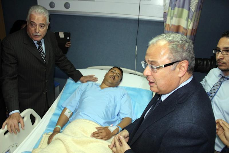 In this Sunday, Feb. 16, 2014 photo released by the Office of the South Sinai Governor, shows the Governor of South Sinai, Major General Khaled Foda, left, and Egyptian Minister of Tourism Hesham Zazou, second right, visit an unidentified Egyptian who was wounded in an explosion as a bus attempted to travel into Israel from Egypt near the Taba border crossing on Sunday, at a hospital in Sharm el-Sheik, South Sinai, Egypt. An explosion tore through a bus filled with South Korean sightseers in the Sinai Peninsula on Sunday, killing at least four people and raising fears that Islamic militants have renewed a bloody campaign to wreck Egypt's tourism industry. The bombing near the tip of the Red Sea's Gulf of Aqaba was the first attack against tourists in Sinai in nearly a decade. (AP Photo/Office of the South Sinai Governor )