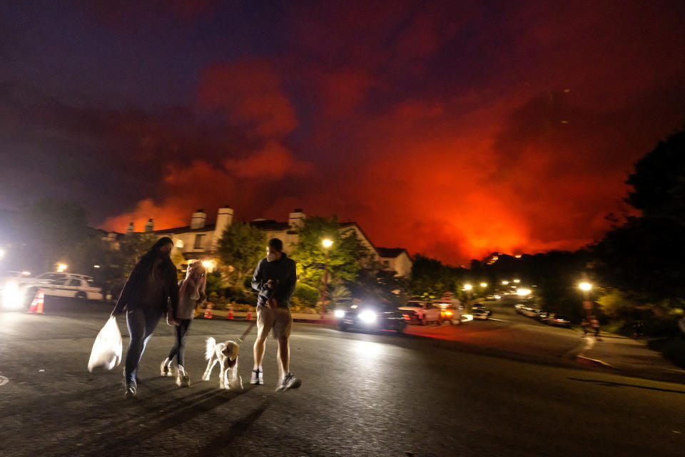 Residents walk a dog as a brush fire burns behind homes in the Pacific Palisades area of Los Angeles on Saturday, May 15, 2021. (AP Photo/Ringo H.W. Chiu)