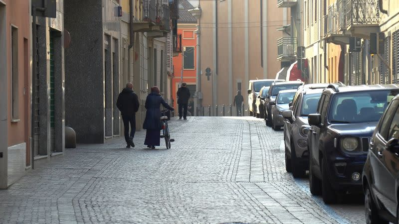 People walk down an empty street in the village of Codogno after officials told residents to stay home and suspend public activities as 14 cases of coronavirus are confirmed in northern Italy