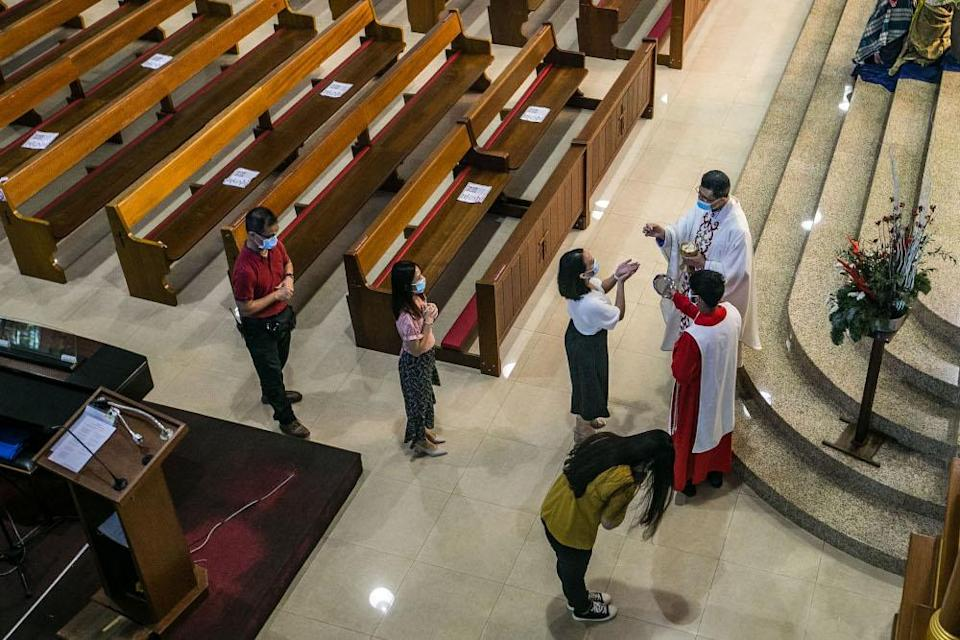 Churchgoers receive communion during Christmas mass at the Church of Divine Mercy in Shah Alam December 25, 2020. — Picture by Firdaus Latif
