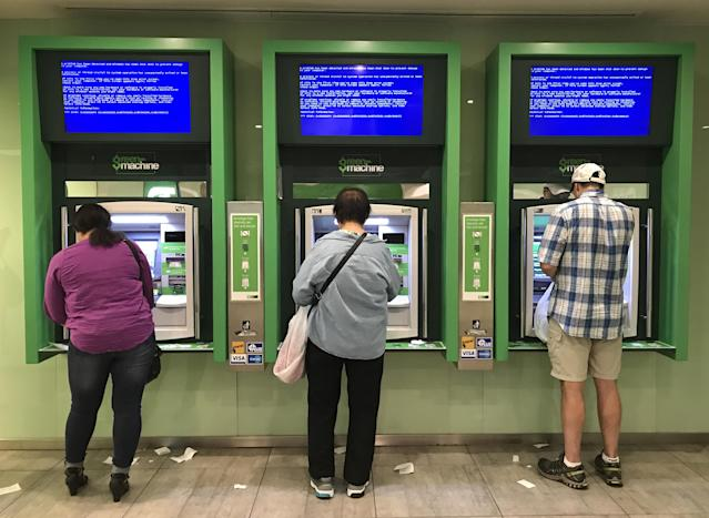 Customers use Toronto Dominion (TD) Bank ATM cash machines under video information screens showing a computer error in Toronto, Ontario, Canada June 24, 2017. (Reuters)