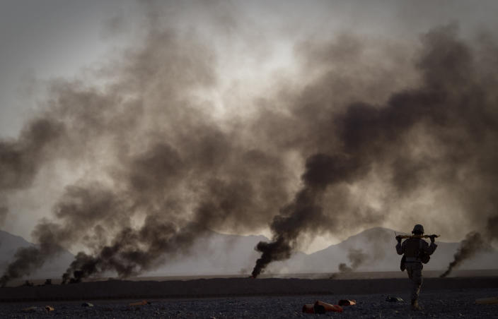 A U.S. Marine walks to pick up food supplies after they were dropped off by small parachutes from a plane outside Forward Operating Base Edi in the Helmand Province of southern Afghanistan on June 9, 2011. The smoke in the background comes from burning parachutes the Marines destroy after they reached the ground. (AP Photo/Anja Niedringhaus, File)