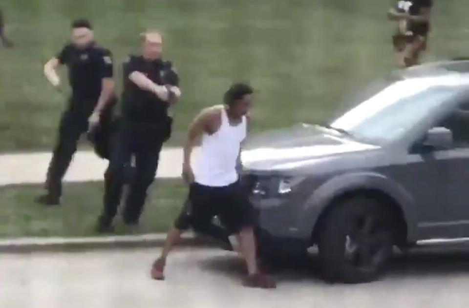 officer points gun at jacob blake's back with another officer behind him