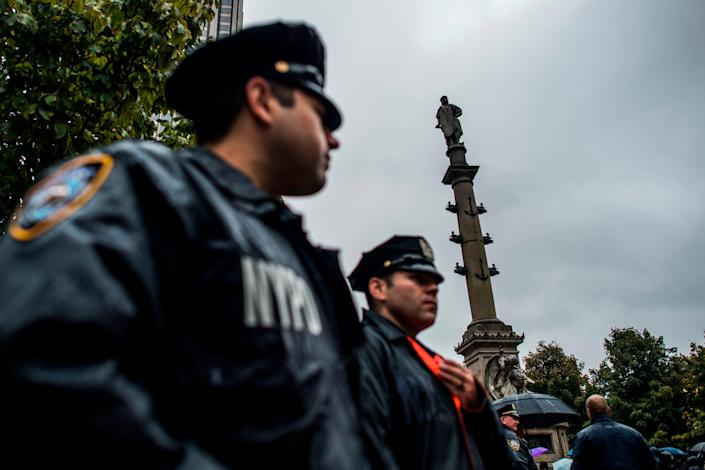 New York Police Department officers stand alert near the statue of Christopher Columbus at Columbus Circle in New York on October 9, 2017, during a protest.