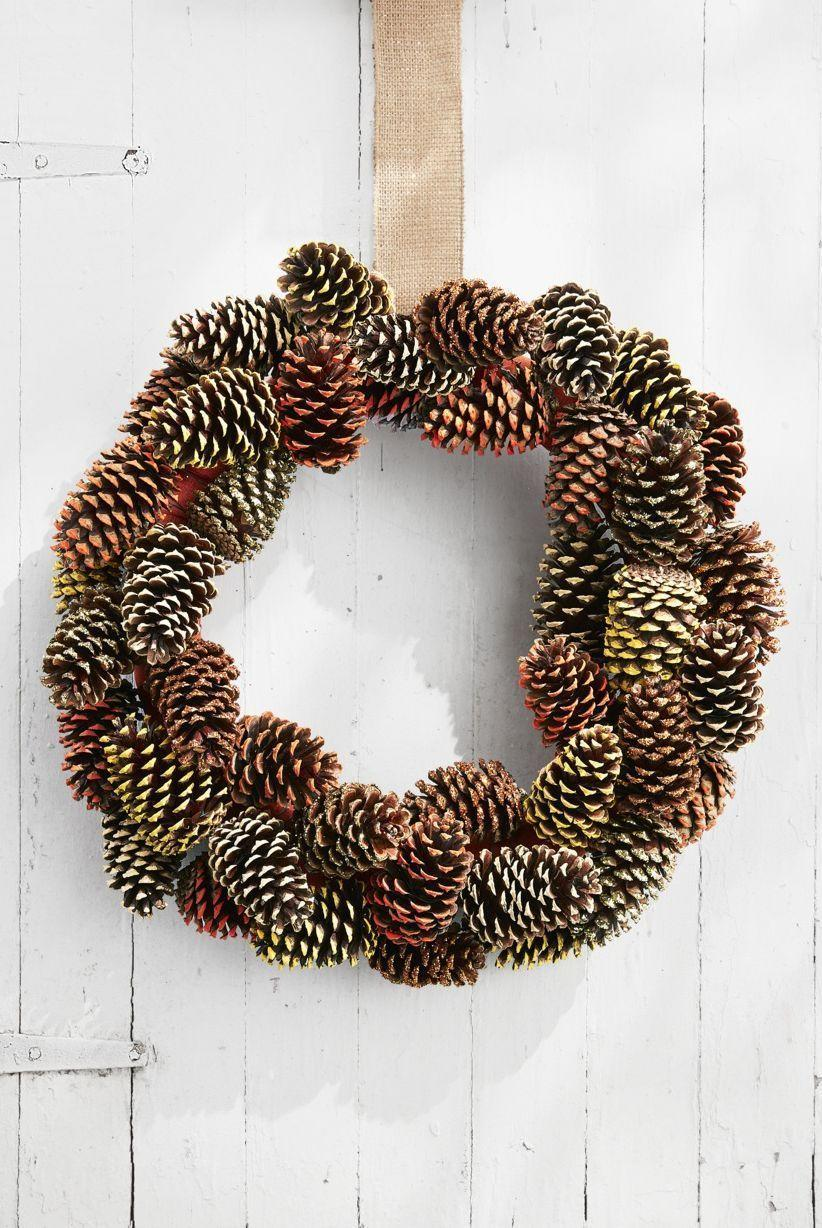 """<p>Let your guests in on all the festive fun happening just beyond the doorway with this pine cone wreath. You can even make it last-minute with a few <a href=""""https://www.countryliving.com/diy-crafts/how-to/g312/all-about-pinecones-1206/"""" rel=""""nofollow noopener"""" target=""""_blank"""" data-ylk=""""slk:pine cones"""" class=""""link rapid-noclick-resp"""">pine cones</a> gathered from your own yard.</p><p><strong>Make the Wreath: </strong>Wrap a 16-inch wreath form with burlap ribbon and loop a piece around the wreath form for hanging. Paint the tips of 40 pine cones in fall colors such as orange, yellow, and beige with acrylic paint. Brush the tips of 10 pine cones with matte Mod Podge and sprinkle with gold and copper glitter. Once dry, wrap an 18-inch length of floral wire around the base of each pinecone and twist tie around the wreath form to secure, layering and overlapping them as you go.</p><p><a class=""""link rapid-noclick-resp"""" href=""""https://www.amazon.com/Laribbons-Burlap-Fabric-Craft-Ribbon/dp/B0046UV3CO/?tag=syn-yahoo-20&ascsubtag=%5Bartid%7C10050.g.1371%5Bsrc%7Cyahoo-us"""" rel=""""nofollow noopener"""" target=""""_blank"""" data-ylk=""""slk:SHOP BURLAP RIBBON"""">SHOP BURLAP RIBBON</a></p>"""
