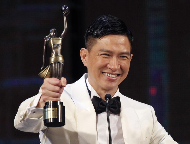 Hong Kong actor Cheung Ka Fai raises the trophy after winning the Best Actor award for his role in the movie ' The Unbeatable' at the 33rd Hong Kong Film Awards in Hong Kong, Sunday, April 13, 2014. (AP Photo/Vincent Yu)
