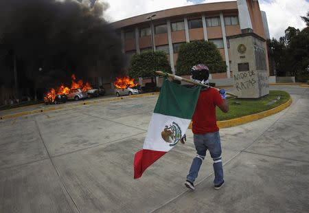 A CETEG member carries the Mexican national flag while walking past vehicles set on fire by fellow CETEG members at a City Congress parking lot in Chilpancingo