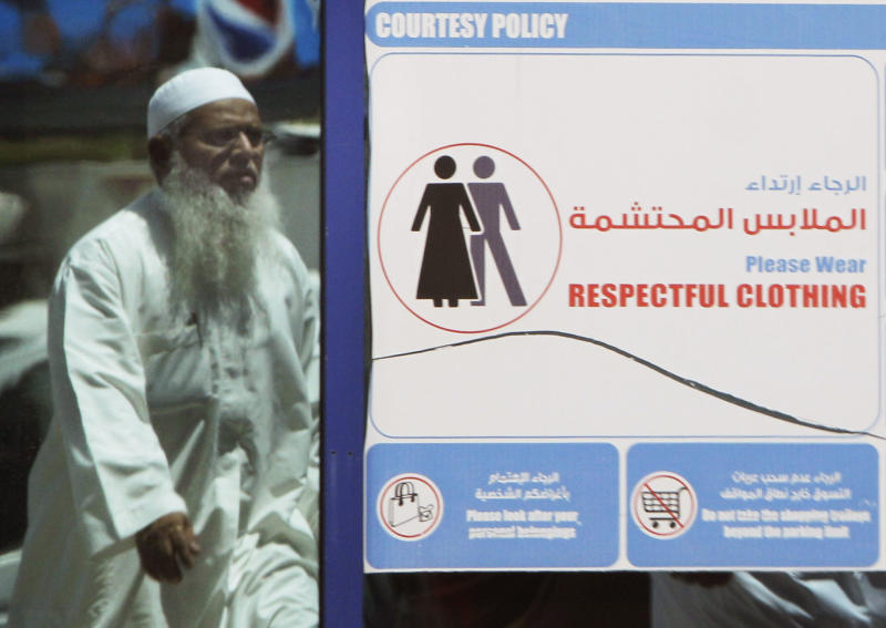 In this photo taken Monday, June 25, 2012, a muslim man passes by a dress code sign at a shopping mall in Dubai , United Arab Emirates. As the numbers of foreigners have increased, so have the stories of them violating the UAE's strict indecency code which limits drinking to bars and nightclubs and bans public displays of affection. (AP Photo/Kamran Jebreili)