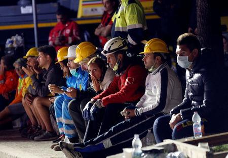 Rescue workers take a rest following an earthquake in Amatrice, central Italy, August 24, 2016. REUTERS/Ciro De Luca