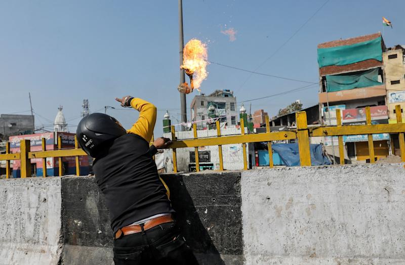 A man throws a petrol bomb at a Muslim shrine during the riots in Delhi on Monday.  (Photo: Danish Siddiqui / Reuters)