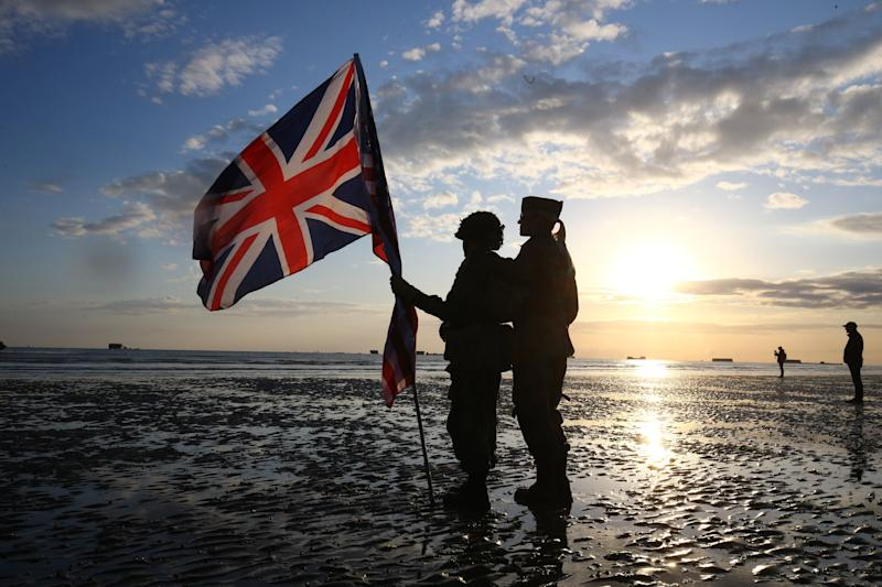 Reenactors dressed in military uniform carry a Union flag at dawn on the beach at Arromanches in Normandy (Picture: PA)
