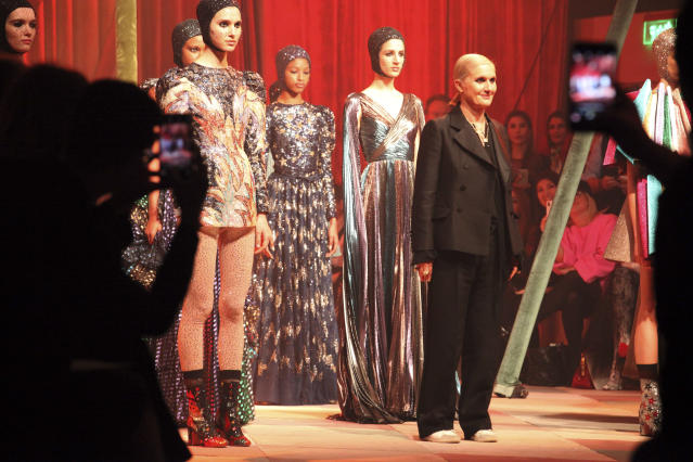 Designer Maria Grazia Chiuri stands with models wearing creations for the Dior Spring/Summer 2019 Haute Couture fashion collection presented in Dubai, United Arab Emirates, Monday, March 18, 2019. (AP Photo/Jon Gambrell)