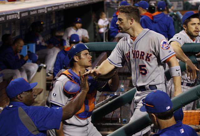New York Mets' David Wright (5) is congratulated by teammates as he comes into the dugout after knocking in the go-ahead run during the 14th inning of a baseball game against the Philadelphia Phillies, Saturday, May 31, 2014, in Philadelphia. The Mets won 5-4. (AP Photo/Chris Szagola)