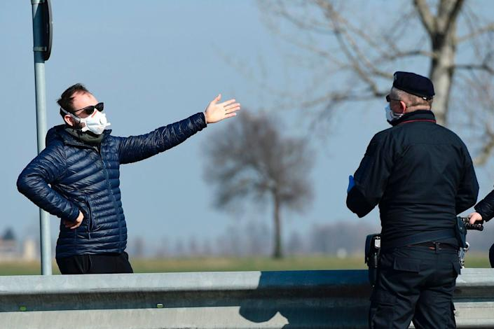 An Italian Carabinieri talks with an inhabitant wearing a respiratory mask at a police check-point few kilometers from the small town of Castiglione d'Adda, southeast of Milan, on February 24, 2020.