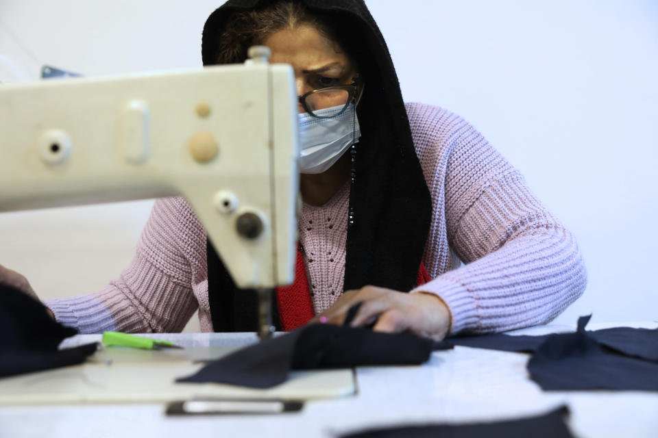 Pari Shasti sews a protective face mask at a workshop of Bavar charity in Tehran, Iran, Monday, Nov. 23, 2020. As the coronavirus pandemic ravages Iran, a women's group hopes to empower its members by helping them make and sell face masks. (AP Photo/Vahid Salemi)