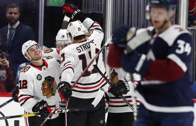 Chicago Blackhawks left wing Alex DeBrincat, left, is congratulated after scoring a goal by centers Jonathan Toews, back right, and Dylan Strome in the first period of an NHL hockey game against the Colorado Avalanche, Saturday, Dec. 29, 2018, in Denver. (AP Photo/David Zalubowski)