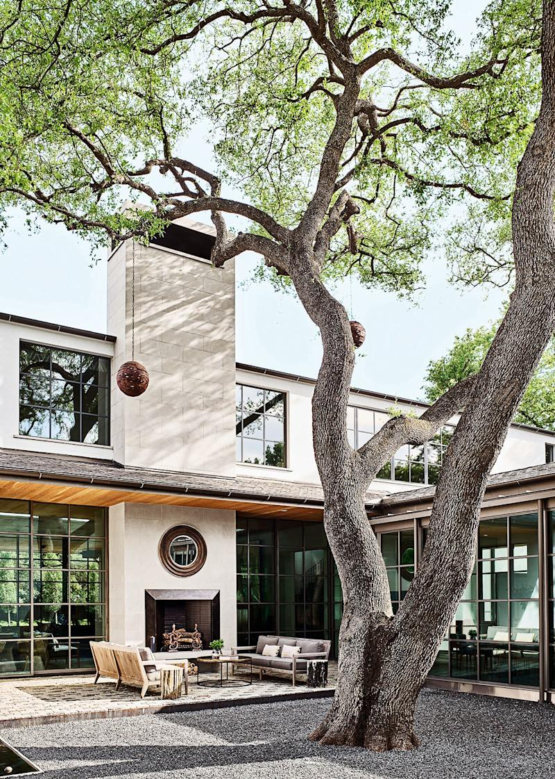 The property's live oak is framed within a central courtyard; the mirror and cocktail table are by Arteriors.