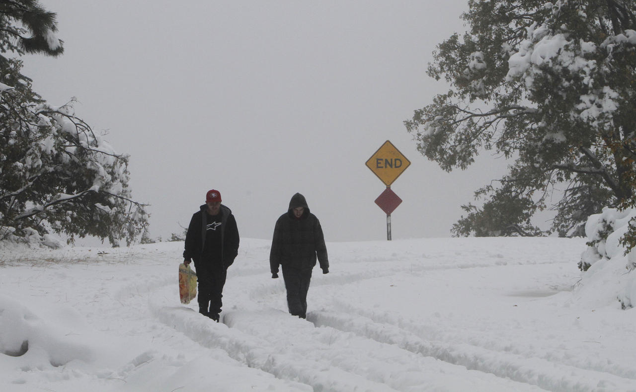 Chris Gilbert, left, and SebastianDrew, walk through the snow after sledding near Blue Canyon, Calif, Monday, Oct. 22, 2012. The first storm of the season swept through Northern California bringing rain to the lower elevations and snow in the mountains. (AP Photo/Rich Pedroncelli)