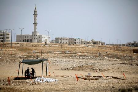 A mosque is seen in the background, as archaeology workers stand beneath a shade near the remains of a mosque, discovered by the Israel Antiquities Authority, which they say is one of the world's oldest, in the outskirts of the Bedouin town of Rahat