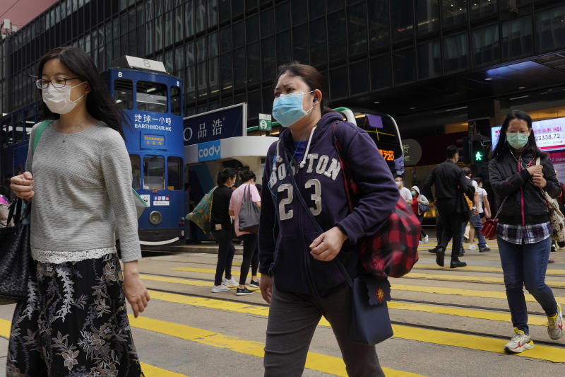 People wearing face masks walk at a down town street in Hong Kong Wednesday, March 25, 2020. For most, the coronavirus causes only mild or moderate symptoms, such as fever and cough. But for a few, especially older adults and people with existing health problems, it can cause more severe illnesses, including pneumonia. (AP Photo/Vincent Yu)