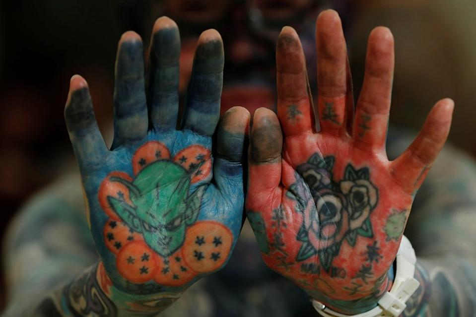 A man shows his tattooed palms to the camera