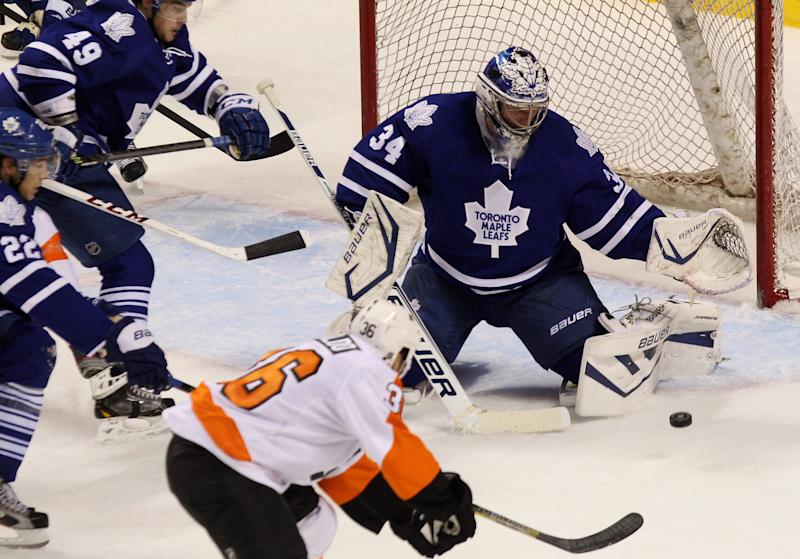 Toronto Maple Leafs' goalie James Reimer (34) makes a save on Philadelphia Flyers' Zack Rinaldo (36) during first-period NHL hockey preseason game action on Sunday, Sept. 15, 2013, in London, Ontario. (AP Photo/The Canadian Press, Dave Chidley)
