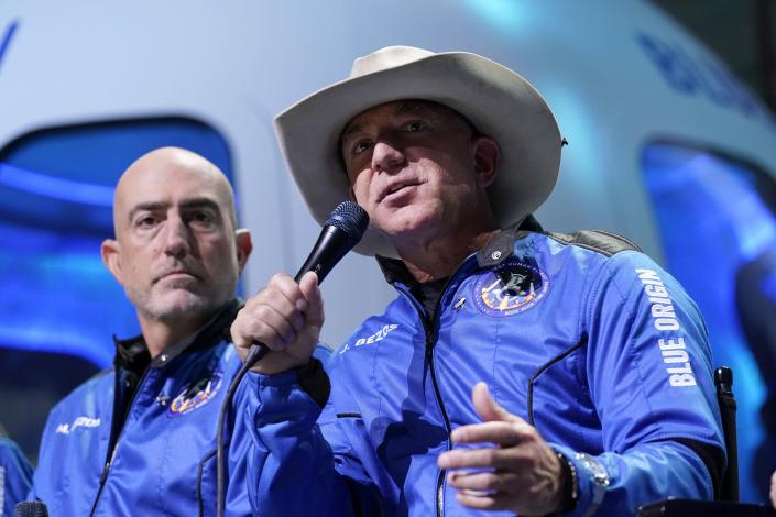 Mark Bezos, left, listens as his brother Jeff Bezos, founder of Amazon and space tourism company Blue Origin, describes the experience after their launch from the spaceport near Van Horn, Texas, Tuesday, July 20, 2021. (AP Photo/Tony Gutierrez)