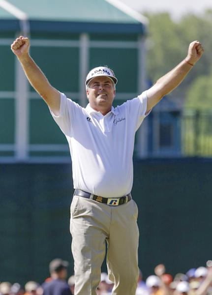 Kenny Perry lifts his arms in celebration on the 18th green Sunday, July 14, 2013, after sinking his last putt and winning the U.S. Senior Open golf tournament in Omaha, Neb. (AP Photo/Nati Harnik)