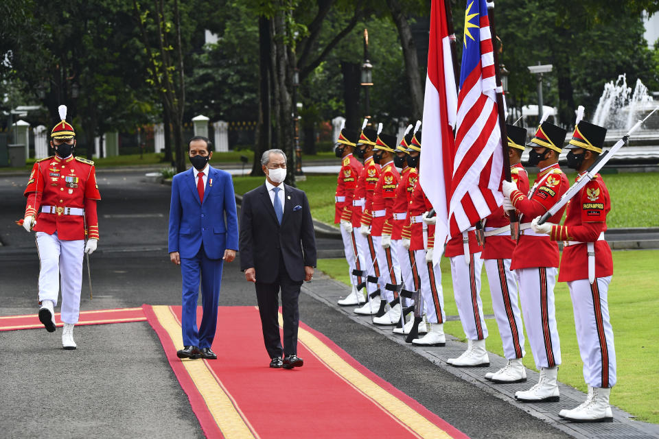 In this photo released by Indonesian Presidential Palace, Malaysian Prime Minister Muhyiddin Yassin, center, walks with Indonesian President Joko Widodo as they inspect honor guards during their meeting at Merdeka Palace in Jakarta, Indonesia, Friday, Feb. 5, 2021. Yassin is currently on a two-day visit in the country. (Agus Suparto, Indonesian President Palace via AP)