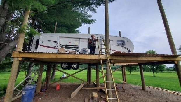 Tina Arthurs and dog Buddy Love sit in the newly perched RV-treehouse that she and her husband, Paul, built to avoid spring floodwater from the St. John River. (Shane Fowler/CBC News - image credit)