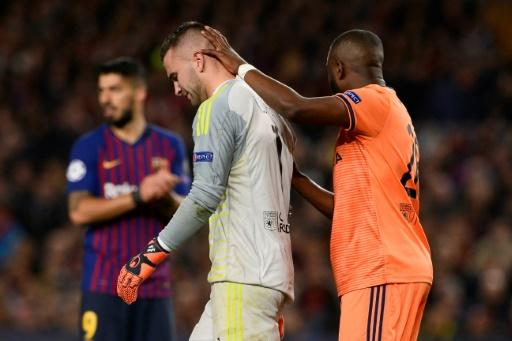 Lyon goalkeeper Anthony Lopes is consoled by one of his teammates as he leaves the field injured and in tears