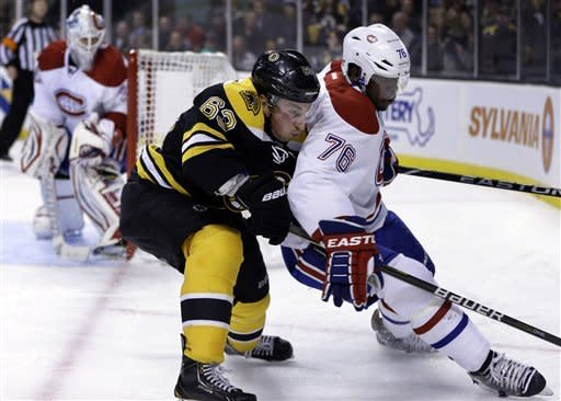 Boston Bruins left wing Brad Marchand (63), center, keeps pressure on Montreal Canadiens defenseman P.K. Subban (76), right, as Canadiens goalie Peter Budaj (30), of Slovakia, looks on at left, in the second period of an NHL hockey game at the TD Garden, in Boston, Sunday, March 3, 2013. (AP Photo/Steven Senne)