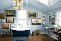"""<p>Themes work especially well in interiors when inspired by your own passions and interests, but with a design-savvy touch. This master bathroom designed by <a href=""""https://www.alexandraangle.com/"""" rel=""""nofollow noopener"""" target=""""_blank"""" data-ylk=""""slk:Alexander Angle"""" class=""""link rapid-noclick-resp"""">Alexander Angle</a> is the perfect example. His client had a large collection of ship paintings, so they decided to anchor the master bath with them. The vintage trunks, light blue walls, and gold pendant are tasteful nods to maritime adventure. </p>"""