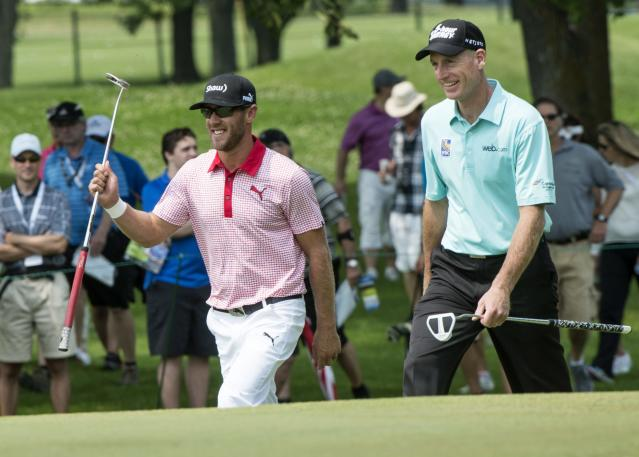 Graham DeLaet, left, of Canada, walks up the the 9th green with Jim Furyk during second round play at the Canadian Open golf championship Friday, July 25, 2014 in Montreal. (AP Photo/The Canadian Press, Paul Chiasson)
