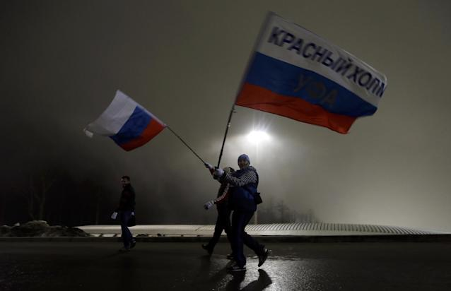 Russian fans walk through Sanki Sliding Center in the fog during the men's two-man bobsled competition at the 2014 Winter Olympics, Sunday, Feb. 16, 2014, in Krasnaya Polyana, Russia. (AP Photo/Natacha Pisarenko)