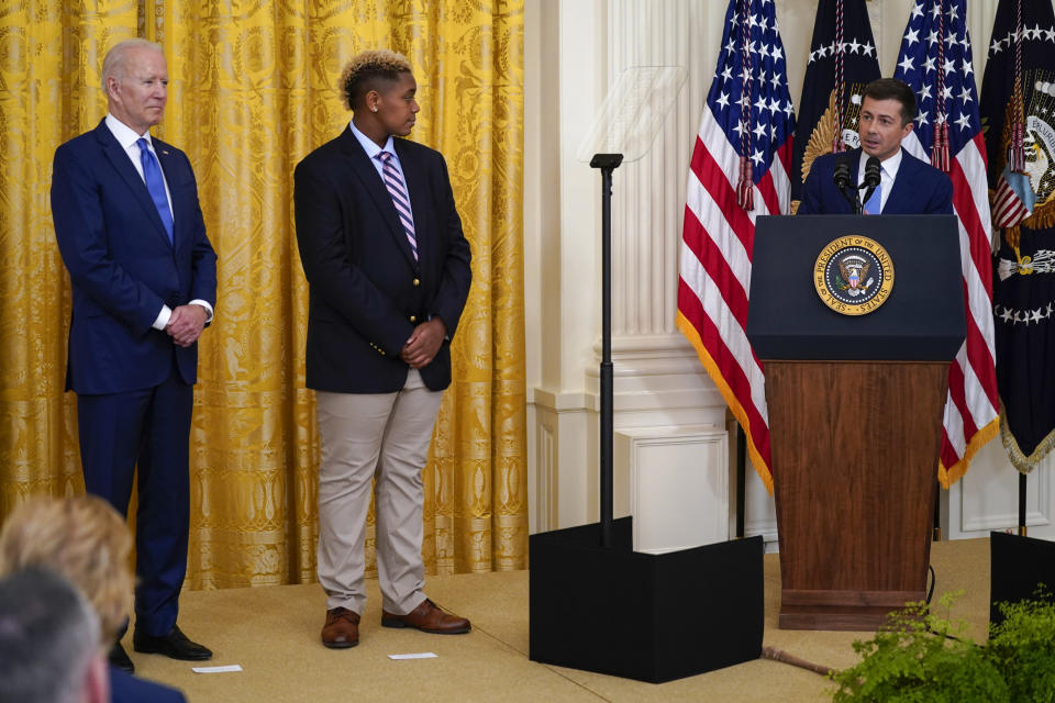 President Joe Biden stands with Ashton Mota, of the GenderCool Project, as Transportation Secretary Pete Buttigieg speaks during an event to commemorate Pride Month, in the East Room of the White House, Friday, June 25, 2021, in Washington. (AP Photo/Evan Vucci)