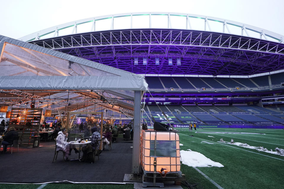 """People eat dinner in an outdoor dining tent set up at Lumen Field, the home of the Seattle Seahawks NFL football team, Thursday, Feb. 18, 2021, in Seattle. The """"Field To Table"""" event was the first night of several weeks of dates that offer four-course meals cooked by local chefs and served on the field at tables socially distanced as a precaution against the COVID-19 pandemic, which has severely limited options for dining out at restaurants in the area. (AP Photo/Ted S. Warren)"""