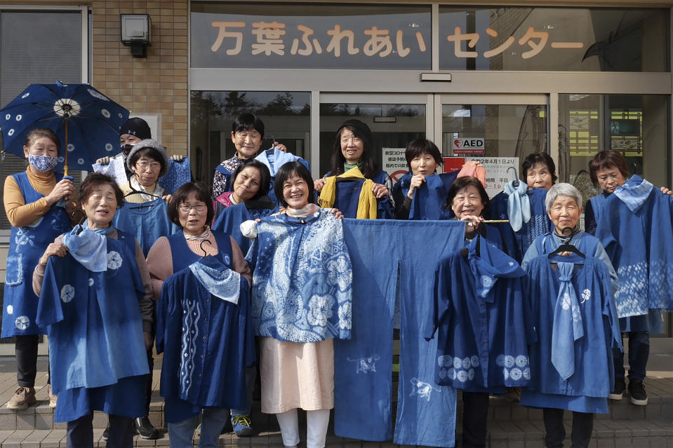 In this image from video, members of Japan Blue hold up their dyed clothes and pose for a photo in front of a community center which was used as an evacuation center when the massive earthquake hit the area in 2011, in Minamisoma, Fukushima Prefecture, northeastern Japan, on Feb. 20, 2021. Because of radiation released by the Fukushima nuclear plant disaster a decade ago, farmers in nearby Minamisoma weren't allowed to grow crops for two years. After the restriction was lifted, two farmers found an unusual way to rebuild their lives and help their destroyed community. They planted indigo and soon began dying fabric with dye produced from the plants. A group called Japan Blue holds workshops that have taught indigo dyeing to more than 100 people each year. (AP Photo/Chisato Tanaka)