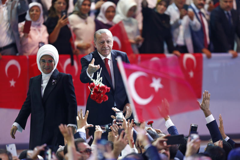 Turkey's President Recep Tayyip Erdogan, center, accompanied by his wife Emine, left, throws flowers to his supporters as he arrives to deliver a speech at his ruling Justice and Development Party (AKP) congress in Ankara, Turkey, Saturday, Aug. 18, 2018. (AP Photo/Burhan Ozbilici)
