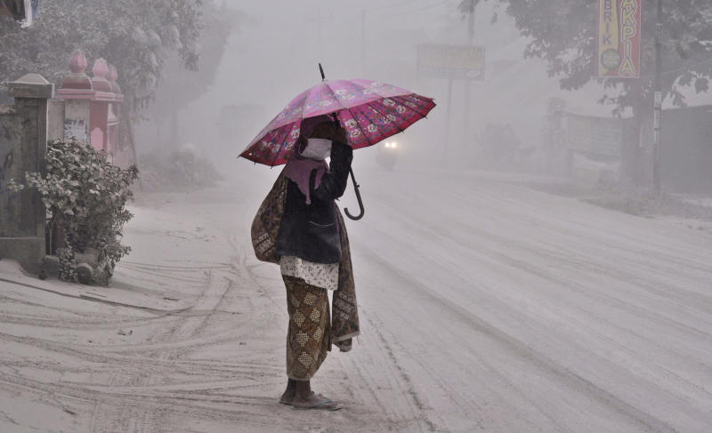 A women walks on a road covered with volcanic ash following an eruption of Mount Kelud, in Yogyakarta, Indonesia, Friday, Feb 14, 2014. Volcanic ash from a major eruption in Indonesia shrouded a large swath of the country's most densely populated island on Friday, closed three international airports and sent thousands fleeing. (AP Photo/Slamet Riyadi)