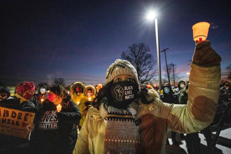 A woman wearing a Black Lives Matter mask raises a candle during a candlelight vigil to honour Andre Hill's memory outside the Brentnell Community Recreation Center in Columbus, Ohio on December 26, 2020. (Stephen Zenner/AFP via Getty Images)