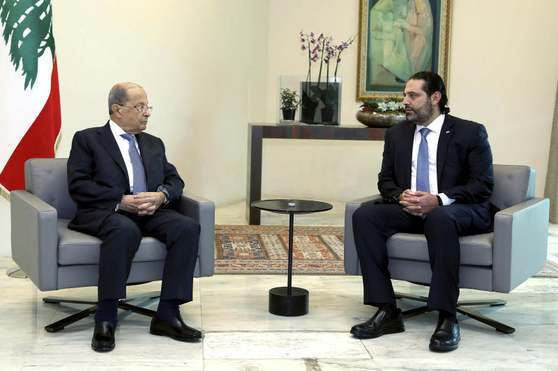 In this photo released by Lebanon's official government photographer Dalati Nohra, Lebanese President Michel Aoun, left, meets with Prime Minister Saad Hariri, ahead of a cabinet meeting, at the presidential palace, in Baabda, east of Beirut, Lebanon, Monday, Oct. 21, 2019. Protesters closed major roads around Lebanon ahead of an emergency Cabinet meeting on Monday, as politicians scrambled to put together a rescue plan for the country's crumbling economy and stem five days of mass anti-government protests.(Dalati Nohra via AP)