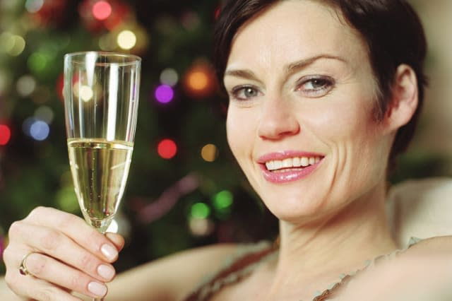 Woman holding glass of wine, smiling, portrait, close-up