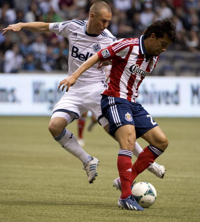 Vancouver Whitecaps FC's Kenny Miller, left, fight for control of the ball with Chivas USA's Carlos Alvarez during the first half of an MLS soccer game in Vancouver, British Columbia, Wednesday, June, 19, 2013. (AP Photo/The Canadian Press, Jonathan Hayward)