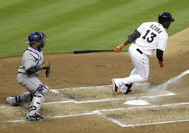 Miami Marlins' Marcell Ozuna (13) hits a single as Colorado Rockies catcher Wilin Rosario, left, looks on in the second inning of a baseball game, Tuesday, April 1, 2014, in Miami. (AP Photo/Lynne Sladky)