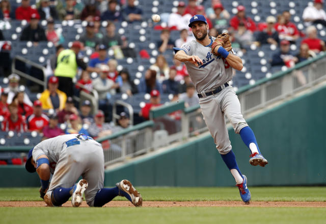 Los Angeles Dodgers third baseman Justin Turner (10) ducks out of the way as shortstop Chris Taylor (3) throws to first base for the out on Washington Nationals' Michael Taylor during the fourth inning of the first baseball game of a doubleheader at Nationals Park, Saturday, May 19, 2018, in Washington. (AP Photo/Alex Brandon)