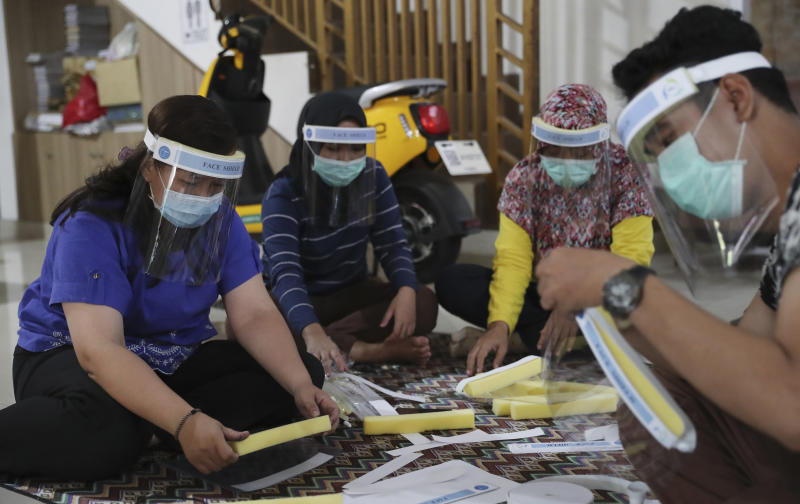 Local community health center workers in their off time assemble face shields to be distributed to co-workers as a precaution against the spread of the coronavirus outbreak in Jakarta, Indonesia Thursday, June 4, 2020. (AP Photo/Achmad Ibrahim)